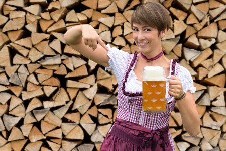 attractive charismatic: Charismatic attractive young Bavarian woman in a dirndl pointing to a tankard of frothy draft beer with a happy smile conceptual of celebrating the Oktoberfest, rustic woodpile background Stock Photo