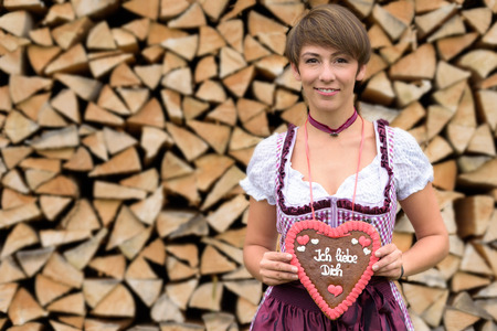 dirndl dress: Attractive young Bavarian woman holding a decorative heart with German text for a sweetheart as she stands in a dirndl dress in front of a neat rustic woodpile, symbolic of love and Valentines Day Stock Photo