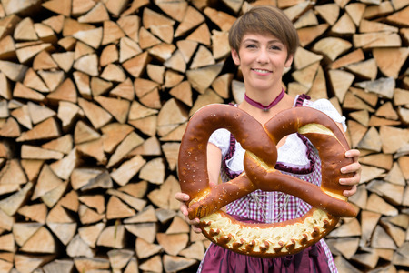 dirndl dress: Smiling young Bavarian woman wearing a traditional dirndl dress stnding in front of a neatly stacked woodpile holding a large decorative knotted pretzel in her hands