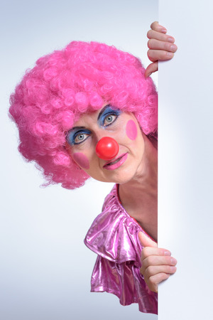 buffoon: Close up Adult Female Clown with Pink Hair, Peeking Out From Behind Poster Paper Against White Background. Stock Photo