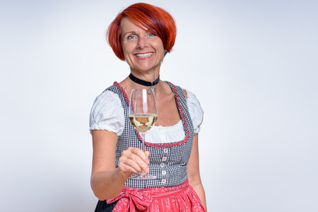 attractive charismatic: Half Body Shot of a Happy German Woman in Dirndl Dress, Holding a Glass of Wine and Smiling at the Camera Against White Wall. Stock Photo