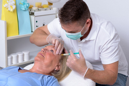clinician: Male Clinician Injecting on the Face of an Adult Female Patient Inside his Clinic.