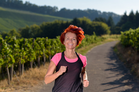 vivacious: Pretty vivacious redhead woman out jogging through country vineyards in evening light smiling as she approaches the camera