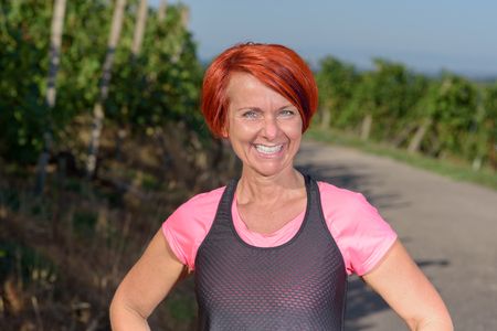 vivacious: Healthy vivacious pretty redhead woman out for her evening jog standing on a road between vineyards smiling at the camera with a lovely charismatic smile Stock Photo