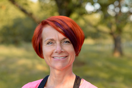 pert: Attractive middle-aged redhead woman with a friendly warm smile standing outdoors in a garden smiling at the camera, head and shoulders close up portrait Stock Photo