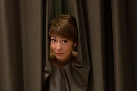 Attractive woman peeking out from drawn curtains framing her face with a quizzical expression Stock Photo