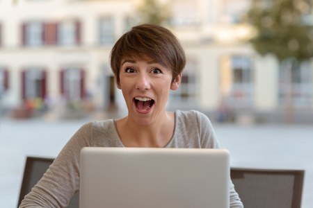 exultant: Excited young woman sitting outdoors at an open-air restaurant reacting to good news on her laptop with an expression of exultant surprise with her mouth wide open