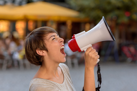 public: Angry young woman yelling into a megaphone as she stands on an urban street venting her frustrations during an open-air rally Stock Photo