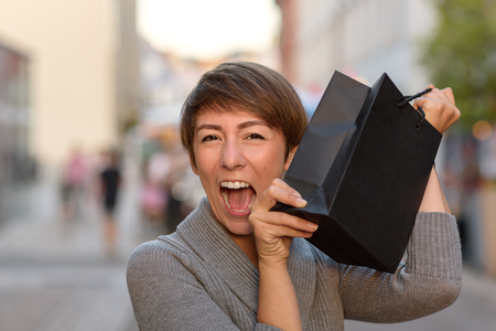 exultant: Excited woman holding up a boutique bag with her recent purchases from an upmarket clothing store showing her pleasure and satisfaction