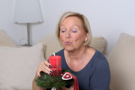 blowing out: Senior lady blowing out a festive red candle on a bed of green foliage decorated with a heart ornament conceptual of Christmas and holidays