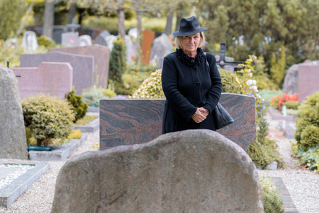 bereaved: Senior lady in mourning at a graveside standing dressed in full black paying her respects to a departed loved one in a large graveyard Stock Photo