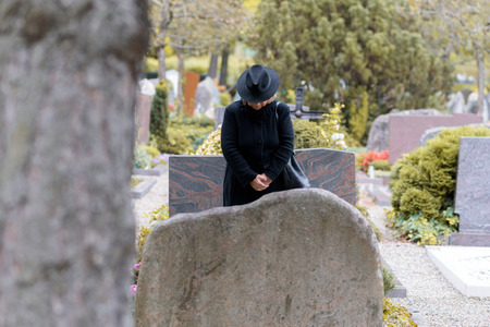 Woman in mourning dressed in full black praying at a graveside standing with her head bowed as she pays respects to a loved one