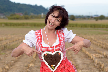 attractive charismatic: Happy young German or Bavarian woman in a dirndl pointing to a decorative iced heart shaped biscuit she is wearing around her neck with a smile, conceptual of love and romance Stock Photo