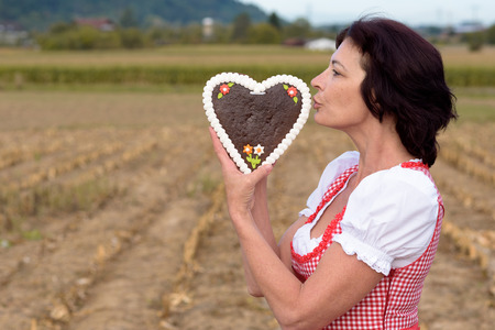 kiss biscuits: Attractive young Bavarian woman wearing a traditional red dirndl standing in a rural field kissing a heart shaped decorative biscuit symbolic of love and romance and Valentines Day