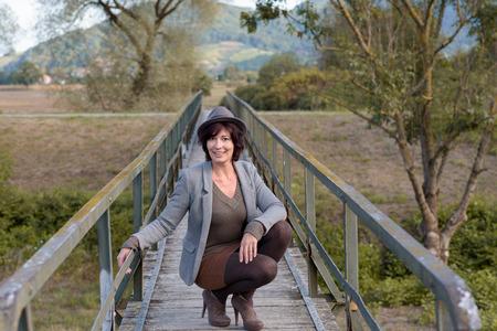 en cuclillas: Chic mujer joven de moda en un sombrero de moda y zapatos de tac�n alto en cuclillas en un puente peatonal que conduce a las monta�as y el paisaje rural sonriendo a la c�mara Foto de archivo