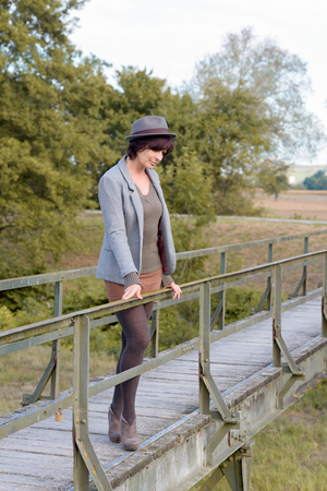 contemplative: Contemplative trendy young woman on a rustic wooden footbridge standing leaning on the rail looking thoughtfully down at the ground below, side view in countryside