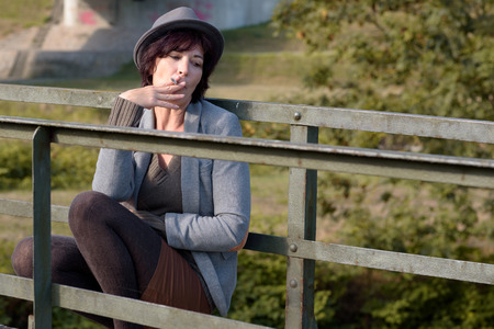 contemplative: Trendy woman sitting outdoors on an old rustic wooden pedestrian bridge in a rural setting smoking a cigarette and looking to the side with a serious contemplative expression Stock Photo