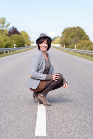 jaunty: Jaunty trendy young woman crouching on the centre white line on a rural road in her stilettos and hat smiling happily at the camera