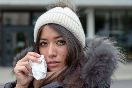 tearful: Sad tearful woman in warm winter fashion holding a handkerchief to her face to dry the tears from her eyes looking into the camera Stock Photo