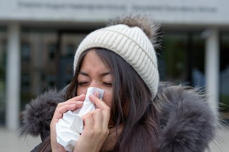gripe: Mujer joven con un invierno de temporada resfriado o gripe que llevaba una chaqueta de peluche y gorra tejida sopla su nariz con un pañuelo blanco al aire libre en una calle urbana