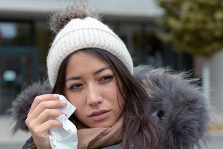 lacrime: Donna triste in lacrime nella moda inverno caldo con un fazzoletto al viso per asciugare le lacrime dai suoi occhi guardando a destra del telaio con gli occhi mancanza lucentezza e l'espressione triste