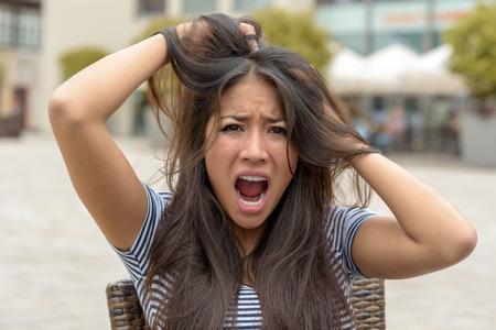 Upset frantic young woman tearing at her hair and yelling in horror as she sits outdoors on a chair in an urban street, close up head and shoulders