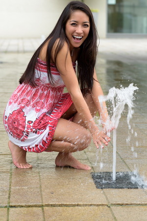 woman kneeling: Playful laughing attractive young woman with long brown hair kneeling barefoot on wet paving alongside a fountain of water holding her hands in the spray