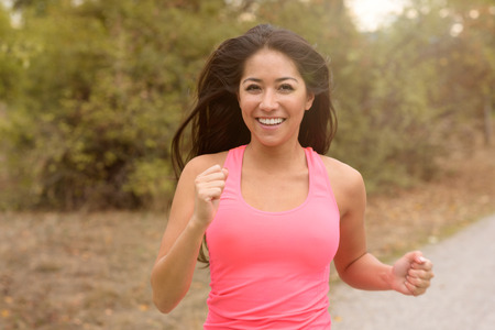 vivacious: Happy vivacious young woman out running along a rural road smiling happily at the camera, close up view in a health and fitness concept