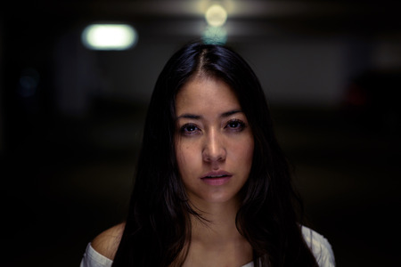 young  brunette: Serious attractive young woman looking at the camera with an unemotional calm expression against a shadowed night background with blurred overhead lights behind her Stock Photo
