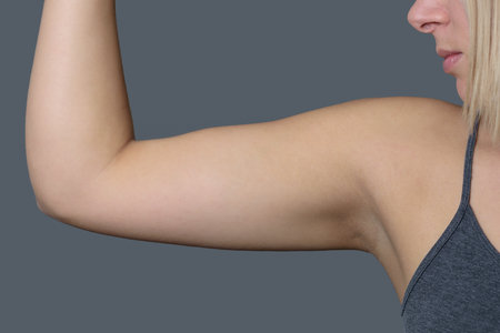 Close up Athletic Young Woman Showing her Arm Muscle Against Grey Wall Background.