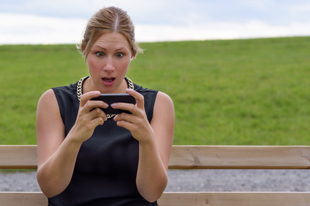 wide eyed: Young woman reacting in shock to an sms of text message on her mobile phone looking at the screen in wide eyed horror as she sits on a park bench outdoors