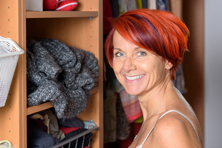 spontaneous expression: Happy Middle Aged Redhead Woman in front of her wardrobe and smiling in to the Camera. Stock Photo