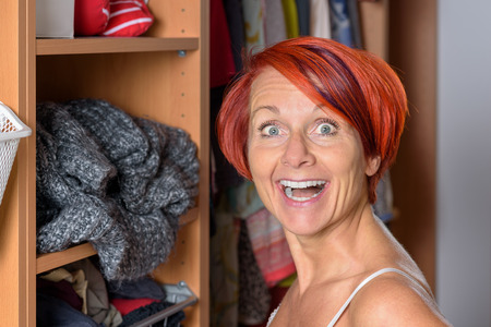 Surprised Middle Aged Redhead Woman in front of her wardrobe