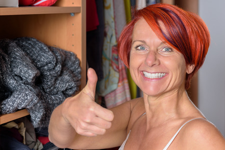 Happy Middle Aged Redhead Woman in front of her wardrobe and Showing Thumbs Up Hand Sign at the Camera.