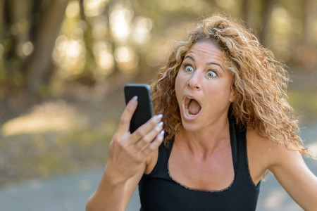 Attractive young woman with gorgeous curly long hair reacting in horror to a text message on her mobile phone staring at it with an aghast expression and mouth open Banque d'images