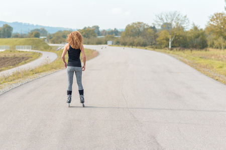 facing away: Muscular sporty young woman on roller blades standing facing away from the camera on a rural road in an exercise and healthy active lifestyle concept