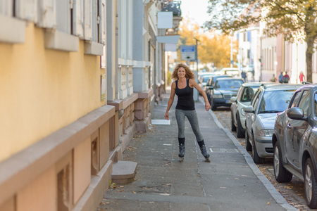 hair roller: Young woman with a fit toned body and curly long hair roller skating down an urban street on rollerblades on the sidewalk alongside parked cars approaching the camera Stock Photo