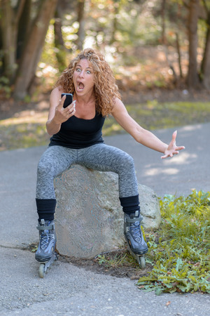 horrified: Horrified attractive sporty young woman staring at her mobile phone with a shocked expression as she sits on a rock at the side of road in her roller blades