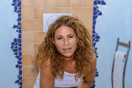 defecating: Young woman sitting on the toilet looking at the camera with a pained expression, conceptual of constipation or diarrhoea, close up head and shoulders Stock Photo
