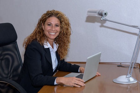lovely businesswoman: Friendly Stylish young businesswoman with a lovely smile sitting working at her desk in the office pausing to look at the camera