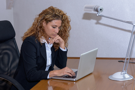 contemplates: Thoughtful young businesswoman working on a laptop computer in an office  as she contemplates information on the screen