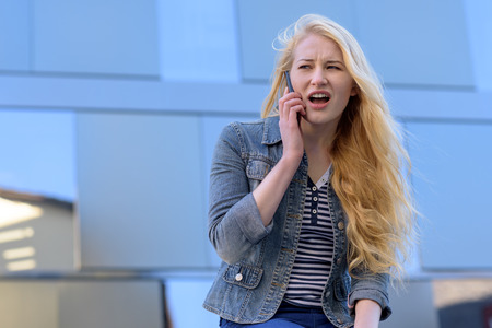 dismay: young blond woman making a telephone call with her mobile