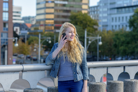 young blond woman phoning with her mobile phone in front of a city skyline Stock Photo