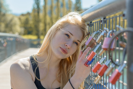 padlocked: Beautiful young blond woman holding padlocks as a sign for endless love with a thoughtful facial expression