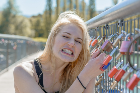 jilted: Beautiful young blond woman holding padlocks as a sign for endless love and pulling it Stock Photo