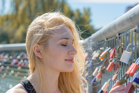 padlocked: Beautiful young blond woman holding padlocks as a sign for endless love