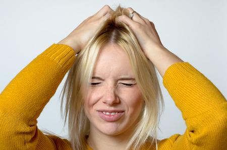 disgusted: Close up Young Woman Scratching her Head Using Two Hands, Showing Disgusted Facial Expression, Against Light Gray Background. Stock Photo