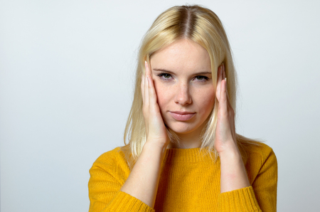 concealing: Close up Pretty Blond Young Woman with headache Looking at the Camera Against Gray Background.
