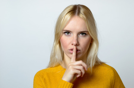 shushing: Close up Pretty Blond Woman Showing Shushing Gesture While Staring at the Camera Against Gray Background. Stock Photo