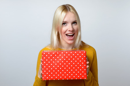 guessing: Happy Blond Young Woman Holding Red Gift Box Against White Background.